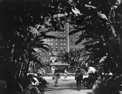 Fountain in Pershing Square, with numerous people reading newspapers on benches June 30, 1939.