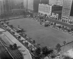 View from above onto Pershing Square showing a large central area of cement or blacktop and plantings on the four sides, Jan. 26, 1954. This is the top of the underground garage before landscaping was added to the central area.